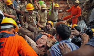 An Indian Fire official shouts for clearing the way as his team rescues an injured from a collapsed building, in Hyderabad, India. At least ten people have been killed and 12 others injured after a two-story hotel collapsed.
