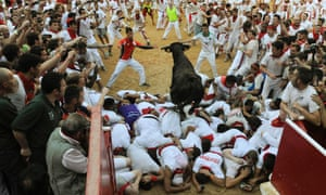 A fighting cow leaps over revellers upon entering the bull ring during the San Fermin festival in Pamplona, Spain.