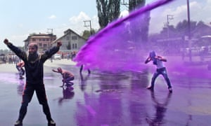 Police uses colored water to disperse Kashmiri government employees during a protest in Srinagar, India.