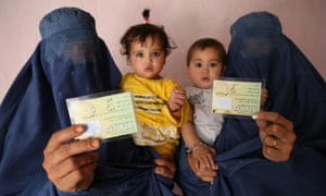 Afghan women show their voter registration cards for presidential elections scheduled for April 2014, in Kabul, Afghanistan.