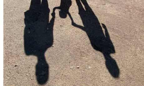 File photograph of shadow of young family holding hands