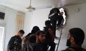 Free Syrian Army fighters climb up a ladder to walk through a hole in a wall during an offensive against forces loyal to Syria's President Bashar al-Assad, in Aleppo.