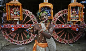 A devotee dressed as Lord Krishna plays the flute ahead of the annual Rath Yatra or Chariot procession of Lord Jagannath in Puri, India. The three idols of Hindu God Jagannath, his brother Balabhadra and sister Subhadra are taken out in a grand procession in specially made chariots called raths, which are pulled by thousands of devotees during the Rath Yatra festival.