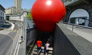 People walk underneath a huge red ball installed in front of the Bel-Air  tower as part of the RedBall Project by US artist Kurt Perschke in Lausanne, Switzerland. The RedBall Project is touring Lausanne from July 3 to 9, changing its location every day.