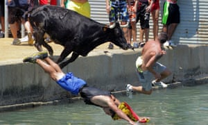 People jump with a bull into the sea during the traditional running of 'Bous a la mar' (Bull in the sea) at Denia's harbour, near Alicante, Spain.