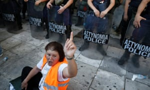 A municipal worker shouts slogans in front of riot police outside the Interior Ministry during a rally against public sector reforms in Athens, Greece.