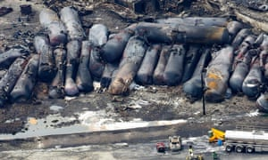A firefighter stands close to the remains of a train wreckage in Lac Megantic, Canada. A driverless, runaway fuel train that exploded in a deadly ball of flames in the centre of a small Quebec town started rumbling down an empty track just minutes after a fire crew had extinguished a blaze in one of its parked locomotives.