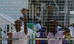 Immigrants stand in a refugee centre after Pope Francis' visit in Lampedusa. Pope Francis celebrated mass on the tiny Sicilian island of Lampedusa to commemorate thousands of migrants who have died crossing the sea from North Africa, underlining his drive to put the poor at the heart of his papacy.