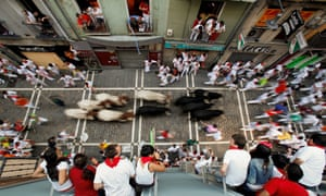 Revellers run with Valdefresno's ranch fighting bulls at Calle Estafeta during the fourth day of the San Fermin Running Of The Bulls festival in Pamplona, Spain.
