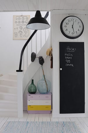homes - norway house: white hallway with stairs with black shade and clock