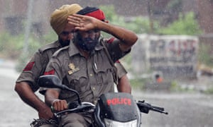 Police officers shield themselves from rain as they ride their bike in Amritsar, India.
