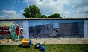 Workers install a panorama by German photographer Kai Wiedenhoefer, showing a wall at the West Bank