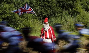 It's ok, Christmas hasn't come early... he's a Tour de France supporter disguised as Santa Claus (who knows why) watching the peloton ride past during  the tenth stage of the race between Saint-Gildas-des-Bois and Saint-Malo in northwestern France.