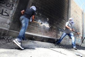 One less brick in the wall: Masked Palestinians use sledge hammers to knock the hole through the Israeli separation wall in the West Bank town of Abu Dis. Photograph: Eloise Bollack/Demotix/Corbis