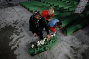 A Bosnian woman lays flowers on a coffin of a baby, among 409 newly identified Srebrenica victims, at the Potocari memorial cemetery near Srebrenica, Bosnia and Herzegovina. A burial ceremony for 409 victims will be held on Thursday, July 11, 2013 in Potocari, on the 18th anniversary of the Srebrenica tragedy when in summer 1995 Bosnian Serb forces stormed the enclave and systematically killed thousands of Bosnian Muslims. Photograph: Amel Emric/AP