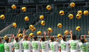 Players throw balls during the Borussia Moenchengladbach team presentation in Moenchengladbach, Germany.