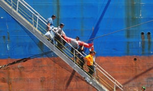 Indonesian police officers carry an injured asylum seeker to disembark a cargo ship.