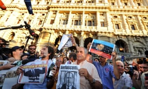 People hold signs as they celebrate the Italian Supreme Court's sentencing of Italian politician Silvio Berlusconi, in front of the Cassation building in Rome, on August 1, 2013.