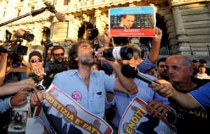A man holds a sign and drinks from a champagne bottle as people celebrate the Italian Supreme Court's sentencing of Italian politician Silvio Berlusconi, in front of the Cassation building in Rome, on August 1, 2013.