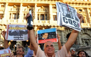 A man holds a sign and a champagne bottle as people celebrate the Italian Supreme Court's sentencing of Italian politician Silvio Berlusconi, in front of the Cassation building in Rome, on August 1, 2013. Italy's top court today confirmed a prison sentence for former prime minister Silvio Berlusconi in the first ever definitive conviction in a tumultuous career for the billionaire tycoon. The court upheld a tax fraud sentence of four years in prison of which three years are covered by an amnesty, even though Berlusconi is certain to be granted community service or house arrest instead.  AFP PHOTO / TIZIANA FABITIZIANA FABI/AFP/Getty Images