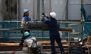 Workers hoist steel bars at a construction site in Tokyo