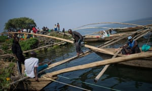 A fisherman walks between traditional wooden boats on the shore of Lake Kivu in Goma, Democratic Republic of the Congo.