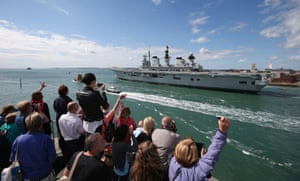 Relatives of Navy personnel wave as HMS Illustrious departs Portsmouth for the Mediterranean