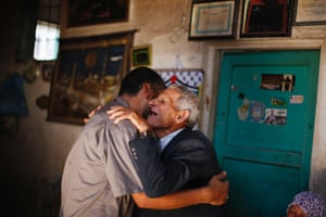 The father and brother of Palestinian prisoner Ateya Abu Moussa, who has been held by Israel for 20 years, hug after hearing news of his expected release in Khan Younis, Gaza Strip. On Monday Israel named 26 Palestinian prisoners to be freed this week under US-backed peace talks deal.