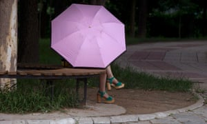 A woman uses an umbrella to avoid the summer sun at a park in Beijing.