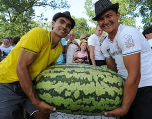 Guess the weight? Two men carry a large watermelon at the Watermelon paradise festival in Strelka village, Russia.