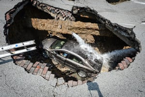 Sinkhole: Toledo, Ohio: A car at the bottom of a sinkhole caused by a broken water pi