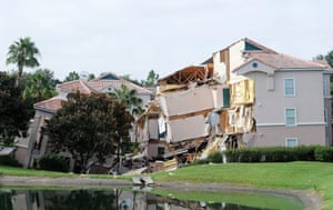 A building sits partially collapsed over a sinkhole at Summer Bay Resort near Disney World in Clermont, Florida. The 40 - 60 foot sinkhole opened up under the resort building overnight.