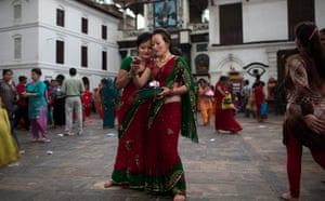 Nepalese Hindu women look at a picture on a phone after worshipping Lord Shiva