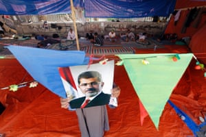 A supporter of Egypt's ousted president Mohammed Morsi hangs his poster at a tent in Nahda Square, where protesters have installed their camp near Cairo University in Giza, Egypt.