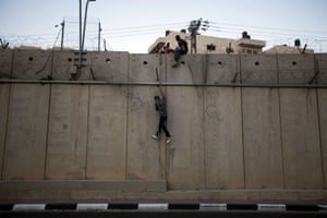 A Palestinian man jumps using a rope to a section of Israel's controversial concrete barrier that separates the West Bank from Jerusalem in Beit Hanina, in Israeli annexed east Jerusalem. Many Palestinians from the West Bank cross illegally into Israel everyday in search for work. Photograph: Ahmad Gharabli/AFP/Getty Images