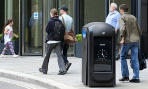 People walk past a 'spy bin' in the City of London