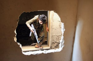 A Free Syrian Army fighter climbs through a hole in a wall in Aleppo's Salaheddine neighbourhood. Photograph: Stringer/Reuters