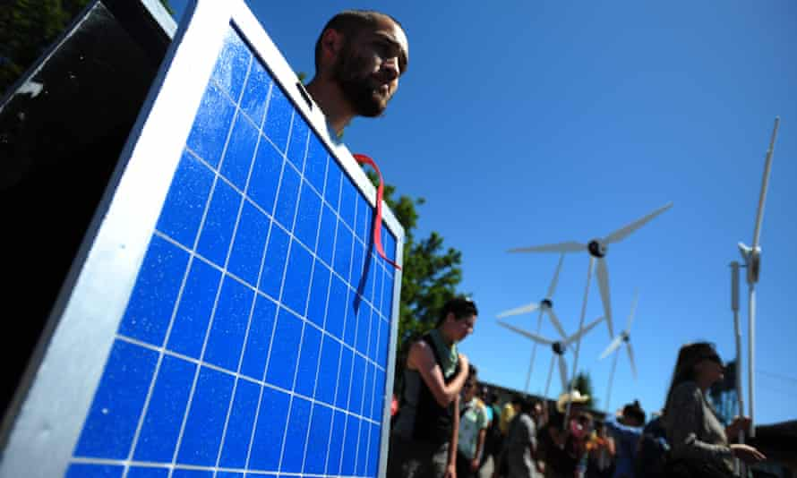 A protester wears a solar panel suit at a rally against fossil fuel exports.