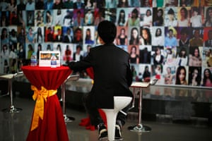China Valentine's day: A man looks at pictures of single people displayed on a board during a matc
