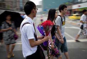 China Valentine's day: A man selling bouquets of roses approaches a couple on a street in Beijing