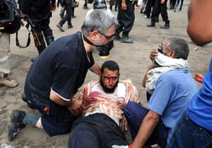 Egyptian camps: A man suffering from tear gas exposure is assisted, after cannisters were f