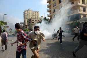 Egyptian camps: Muslim Brotherhood supporters run from tear gas in a street leading to the