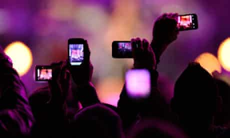 Audience takes photos with their mobile phones during a gig