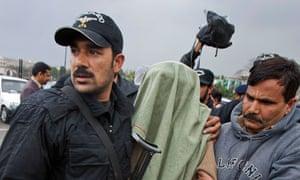 Pakistani security personnel escort a suspected militant to court
