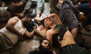 Wounded supporters lie on the floor of a makeshift hospital at Cairo's Nasr City district.