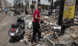 An Egyptian boy collects shoes from the debris left outside the Rabaa al-Adaweya Mosque.