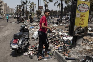 Egypt after crackdown: A boy collects shoes from the debris left outside the Rabaa al-Adawiya mosq