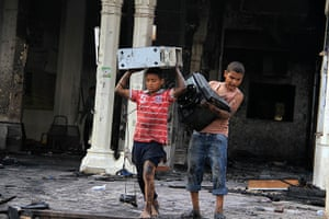 Egypt after crackdown: Children carry computer equipment in the burned remains of the Rabaa al-Ada