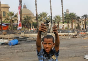 Egypt after crackdown: A child holds empty teargas canisters among the debris of a protest camp in Nahda Square