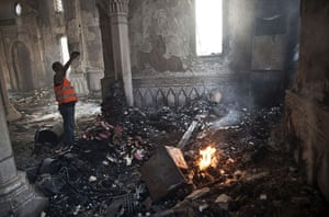 Egypt after crackdown: A man stands near a fire as he takes a picture of the damage in the Rabaa al-Adawiya mosque